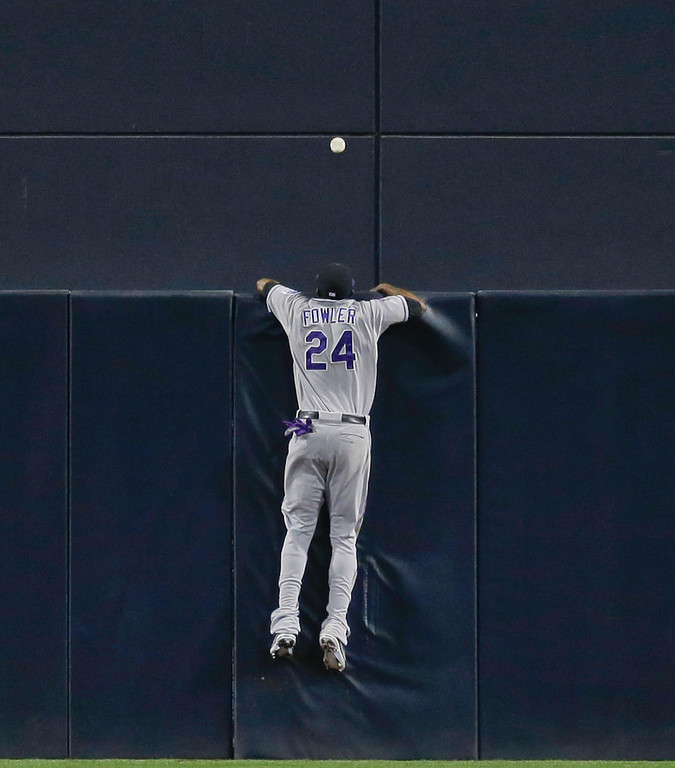 . Colorado Rockies center fielder Dexter Fowler rest on the fence watching a two-run homer by San Diego Padres\' Yonder Alonso during the first inning of a baseball game, Friday, April 12, 2013, in San Diego. (AP photo/Lenny Ignelzi)