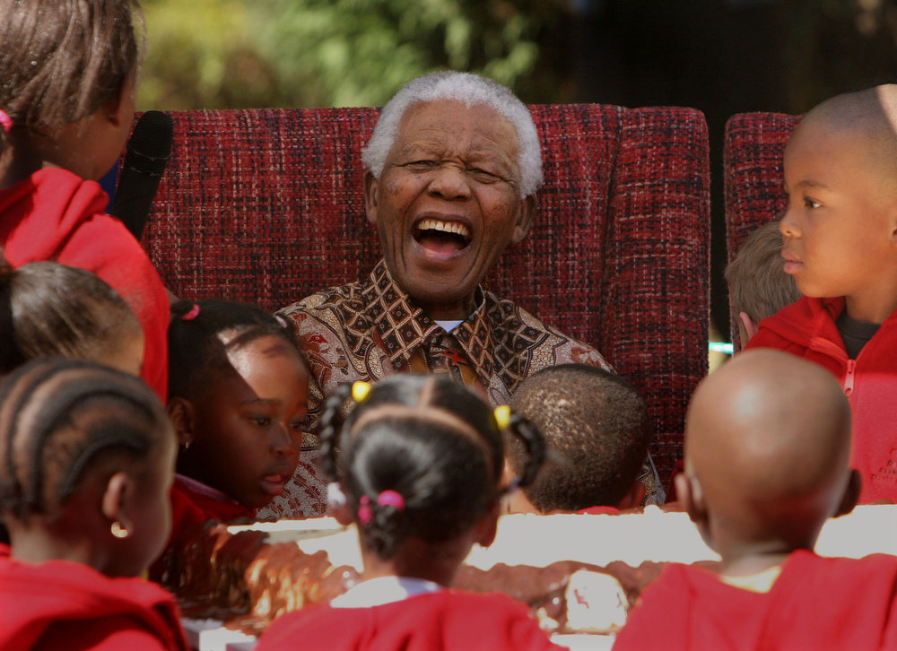 Description of . In this July 24, 2007 file photo, former South African President Nelson Mandela, center, shares a lighter moment ending  his 89th birthday celebrations with children at the Nelson Mandela Children's Fund in Johannesburg.  (AP Photo/Denis Farrell, file)