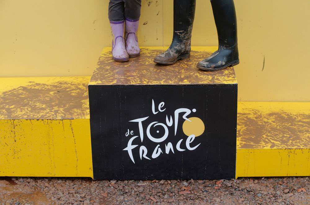 . Children wear rain boots as they watch the start of the sixth stage of the Tour de France cycling race over 194 kilometers (120.5 miles) with start in Arras and finish in Reims, France, Thursday, July 10, 2014. (AP Photo/Christophe Ena)