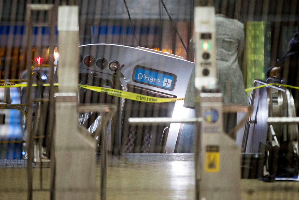 . A derailed Chicago Transit Authority train car rests on an escalator at the O\'Hare Airport station early Monday, March 24, 2014, in Chicago. More than 30 people were injured after the eight-car train plowed across a platform and scaled the escalator at the underground station. (AP Photo/Andrew A. Nelles)