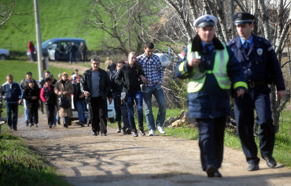 . Unidentified relatives of a victims of a shooting return to their homes in the village of Velika Ivanca, 40 kilometers south of capital Belgrade, on April 9, 2013. A man shot dead 13 relatives and neighbors, including a two-year-old child, in a tiny Serbian village on Tuesday, in the country\'s worst killing spree in two decades.  AFP PHOTO / ALEXA STANKOVIC