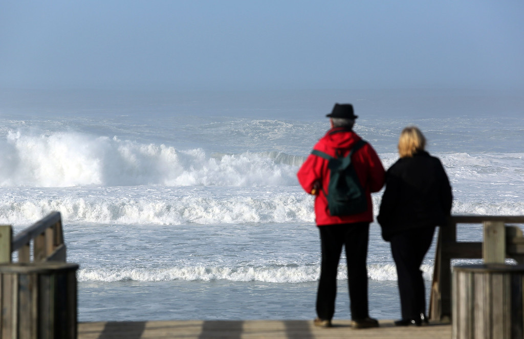 . A couple look at waves on January 7, 2014 along the beach of Mimizan, southwestern France, a day after a massive storm on France\'s western coasts.   NICOLAS TUCAT/AFP/Getty Images