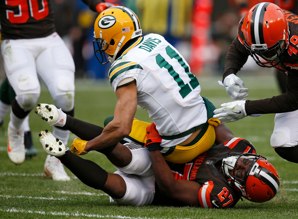 . Green Bay Packers wide receiver Trevor Davis (11) is tackled by Cleveland Browns running back Matt Dayes (27) after a punt return in the second half of an NFL football game, Sunday, Dec. 10, 2017, in Cleveland. (AP Photo/Ron Schwane)