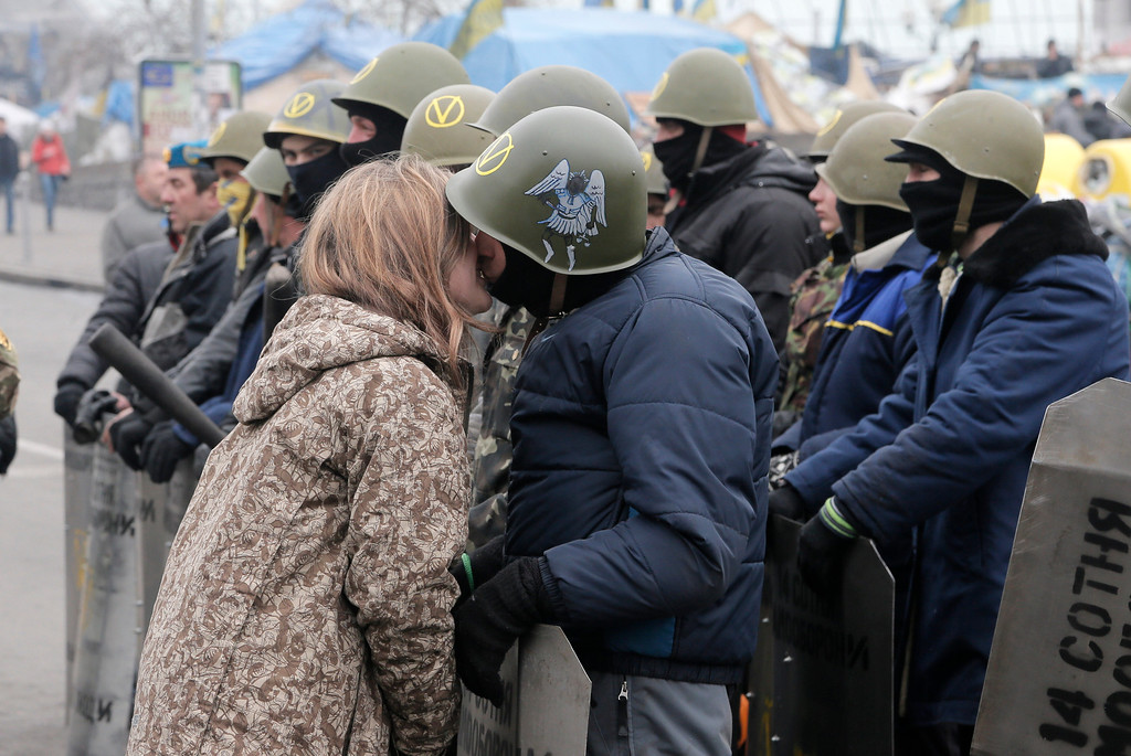 . An opposition protester and his girlfriend shares a kiss on Valentine\'s Day while protesters prepare for a rally in Kiev\'s Independence Square, the epicenter of the country\'s current unrest, Ukraine, Friday, Feb. 14, 2014. Valentine\'s Day is observed on February 14 each year as a special day to celebrate love and romance. (AP Photo/Efrem Lukatsky)