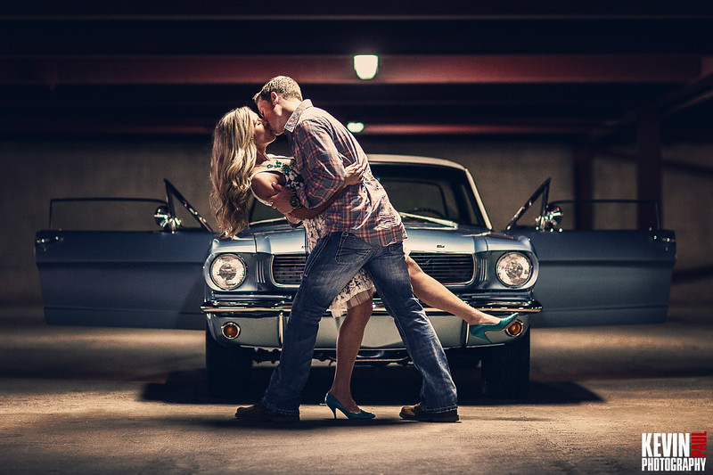 Engagement session shot in a parking garage with a classic Mustang as the backdrop.