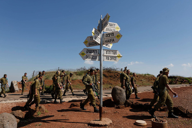 . Israeli soldiers walk past signs pointing out distances to different cities at an observation point on Mount Bental in the Israeli-occupied Golan Heights May 5, 2013.U.N. Secretary-General Ban Ki-moon on Sunday voiced alarm at reports Israel has struck targets inside Syria, but said the United Nations was unable to confirm whether any such attacks had taken place. REUTERS/Baz Ratner