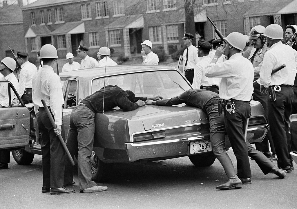 . Holding two looting suspects against the trunk of a police car, city and state police officers move out to enforce a curfew in Memphis, Tenn., March 28, 1968. Violence erupted midway through a march led by Dr. Martin Luther King Jr. in support of striking garbage workers. City officials imposed a curfew throughout the city to begin at 7 p.m. (AP Photo/Jack Thornell)