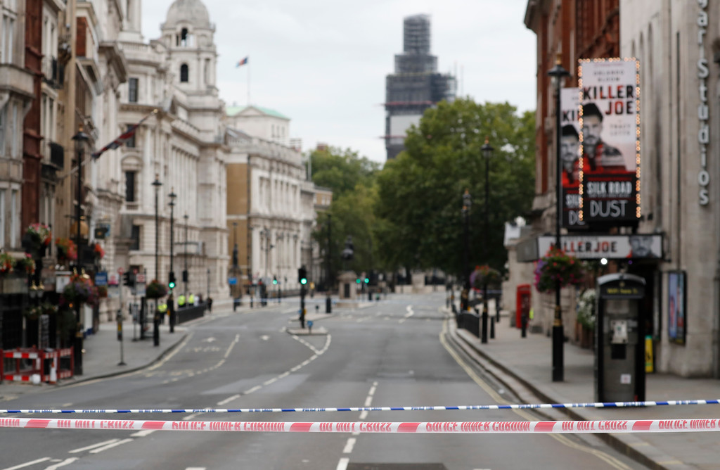 . A deserted road leading to the scene where a car crashed into security barriers outside the Houses of Parliament to the right of a bus in London, Tuesday, Aug. 14, 2018. London police say that a car has crashed into barriers outside the Houses of Parliament and that there are a number of injured. (AP Photo/Frank Augstein)