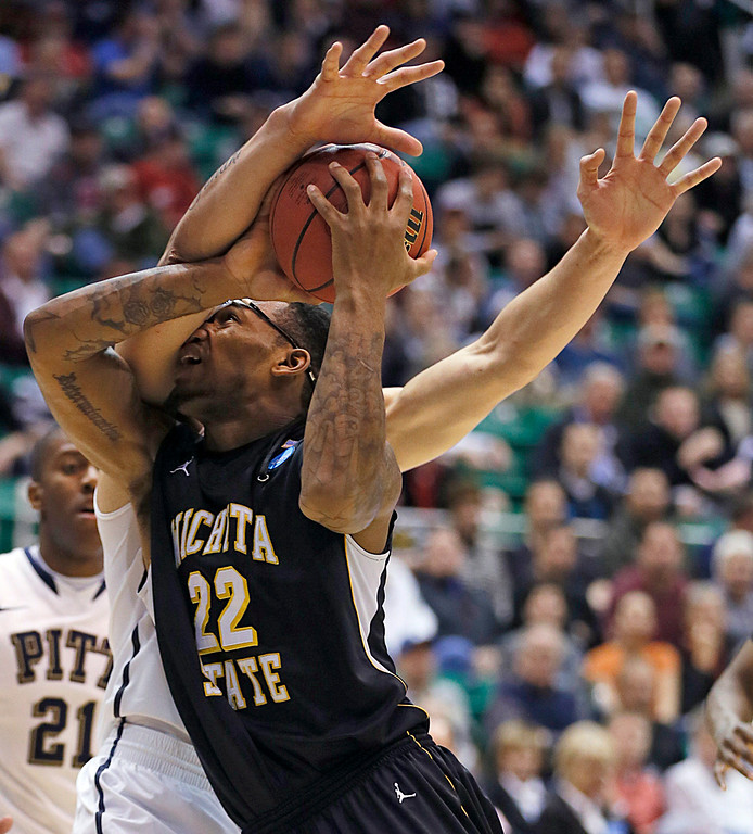 . Wichita State\'s Carl Hall, right, is fouled by Pittsburgh\'s Steven Adams during the second half of a second-round game in the NCAA college basketball tournament in Salt Lake City Thursday, March 21, 2013. (AP Photo/George Frey)