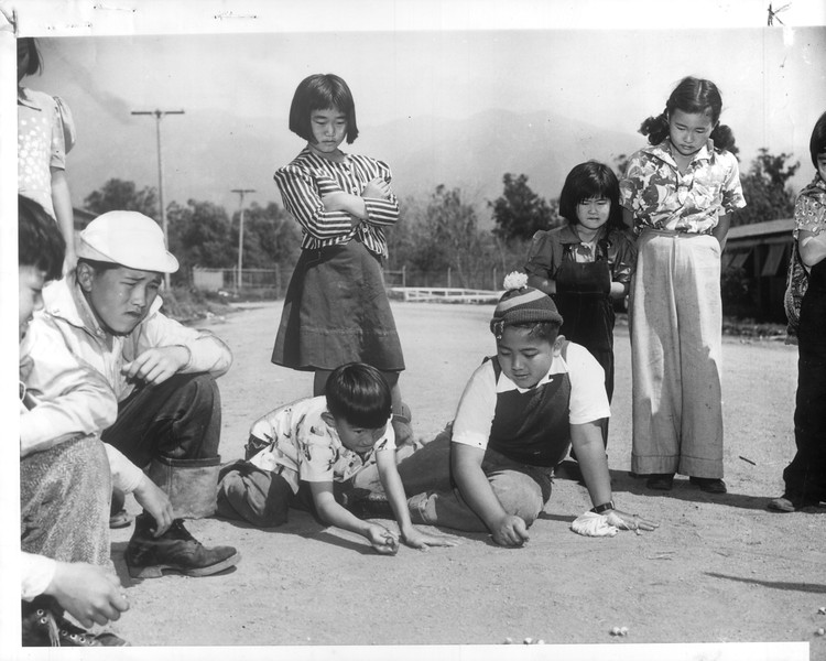 """""""With Sober-faced attentiveness these Japanese girls watch one of the many games of marbles which occupy scores of young evacuees living at the Santa Anita reception depot"""" -- caption on photograph"""