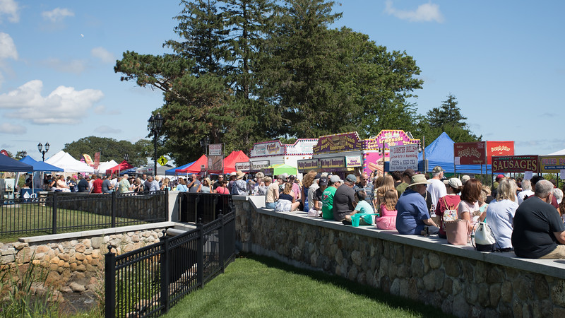 The stone wall bordering the Brewster Gardens served as great seat for eating lunch across from the many Harbor Festival food vendors.  [Wicked Local Photo/Denise Maccaferri]