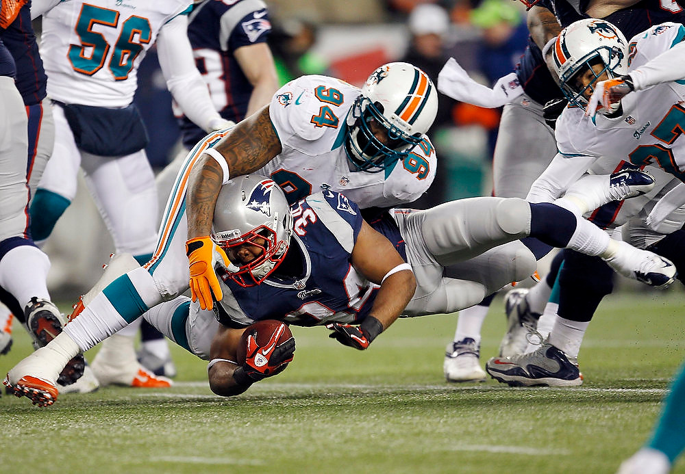 Description of . New England Patriots running back Shane Vereen (C) is brought down by Miami Dolphins Randy Starks (L) and Jimmy Wilson (R) during the first half of their NFL football game in Foxborough, Massachusetts December 30, 2012. REUTERS/Jessica Rinaldi