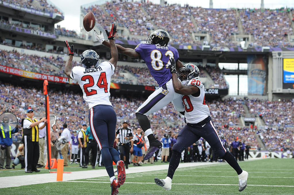 . Cornerback Johnathan Joseph #24 and safety Ed Reed #20 of the Houston Texans defend against wide receiver Torrey Smith #82 of the Baltimore Ravens at M&T Bank Stadium on September 22, 2013 in Baltimore, Maryland.  (Photo by Larry French/Getty Images)