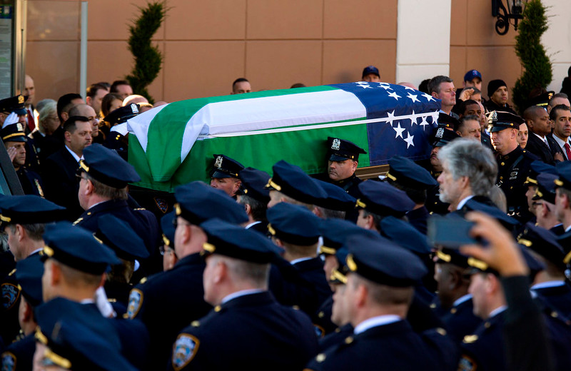 . The body of New York City police officer Rafael Ramos is brought from Christ Tabernacle Church draped in an NYPD flag after his funeral in the Glendale section of Queens, where he was a church member, Saturday, Dec. 27, 2014, in New York. Ramos and his partner, officer Wenjian Liu, were killed Dec. 20 as they sat in their patrol car on a Brooklyn street. The shooter, Ismaaiyl Brinsley, later killed himself.� (AP Photo/Craig Ruttle)