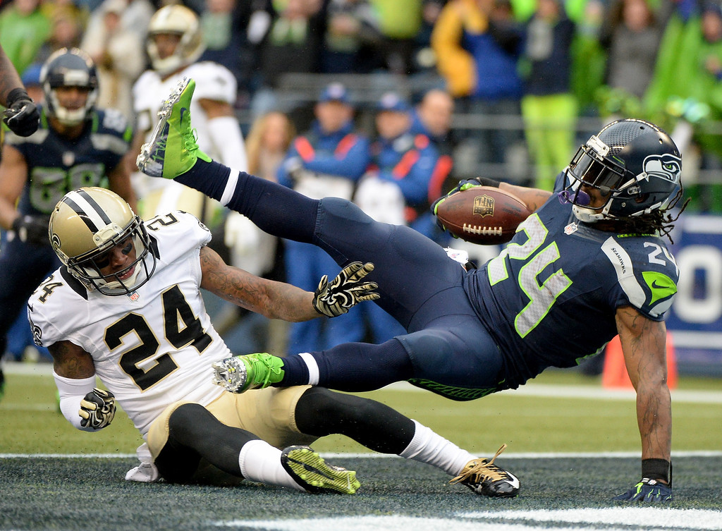 . SEATTLE, WA - JANUARY 11:  Running back Marshawn Lynch #24 of the Seattle Seahawks scores a touchdown on a 15-yard run in the second quarter against cornerback Corey White #24 of the New Orleans Saints during the NFC Divisional Playoff Game at CenturyLink Field on January 11, 2014 in Seattle, Washington.  (Photo by Harry How/Getty Images)