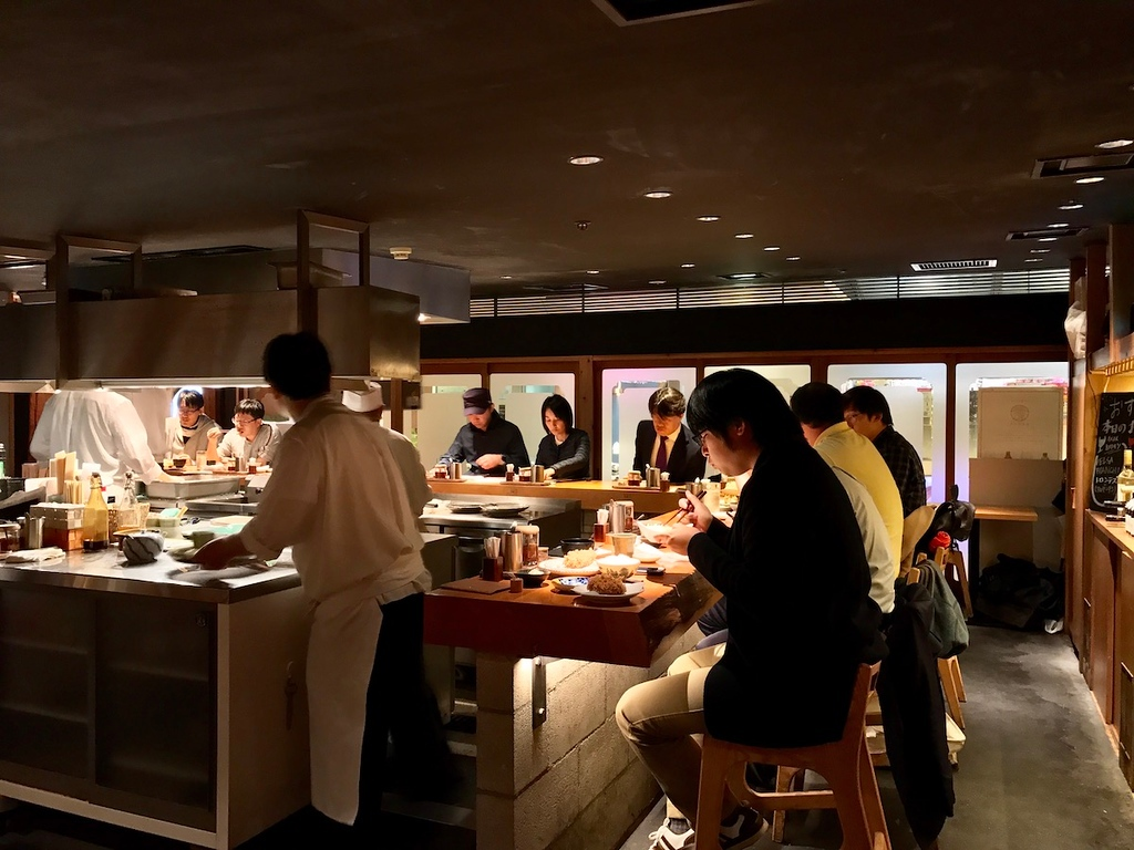 Counter seating around an open kitchen, where you can watch tonkatsu cutlets being fried.