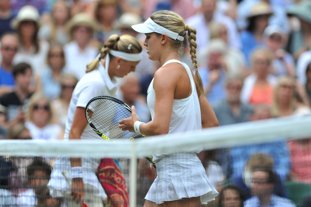 Description of . Czech Republic's Petra Kvitova (L) and Canada's Eugenie Bouchard (R) switch sides after the first game during their women's singles final match on day twelve of  the 2014 Wimbledon Championships at The All England Tennis Club in Wimbledon, southwest London, on July 5, 2014. (GLYN KIRK/AFP/Getty Images)