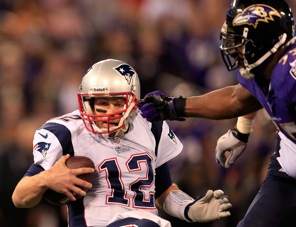 . Quarterback Tom Brady #12 of the New England Patriots is sacked by outside linebacker Terrell Suggs #55 of the Baltimore Ravens during the second half at M&T Bank Stadium on December 22, 2013 in Baltimore, Maryland.  (Photo by Rob Carr/Getty Images)