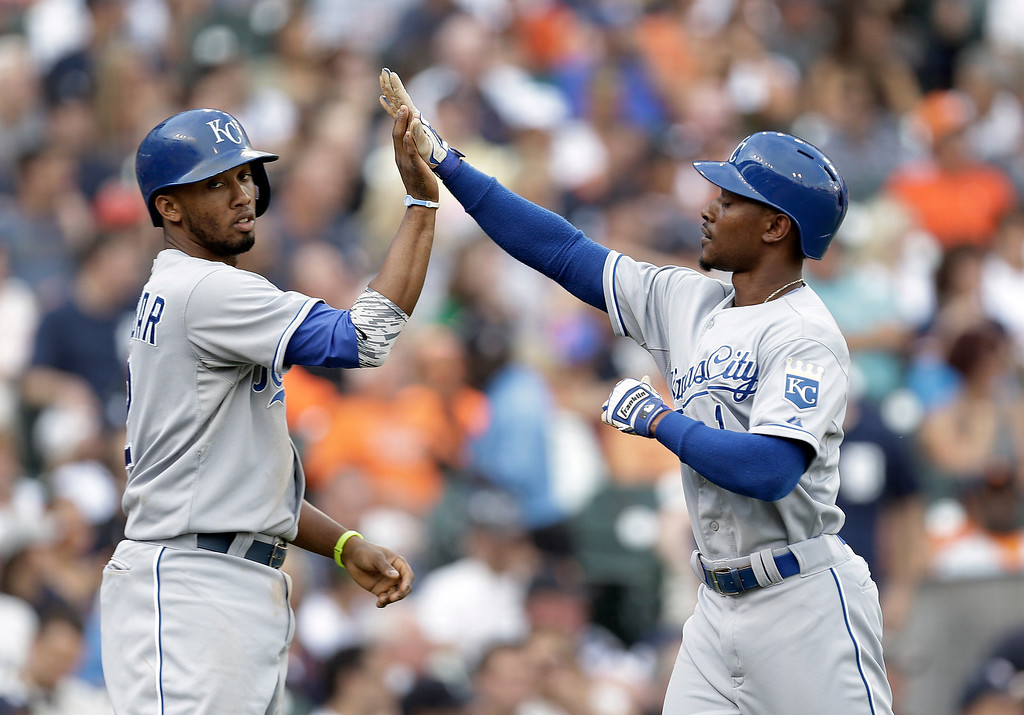 . Kansas City Royals\' Alcides Escobar, left, and Jarrod Dyson celebrate scoring on a Omar Infante single against the Detroit Tigers in the second inning of a baseball game in Detroit, Tuesday, June 17, 2014.  (AP Photo/Paul Sancya)