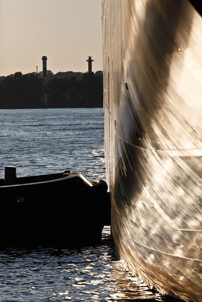 Schlepper drückt Containerschiff in der Sonne Hamburg