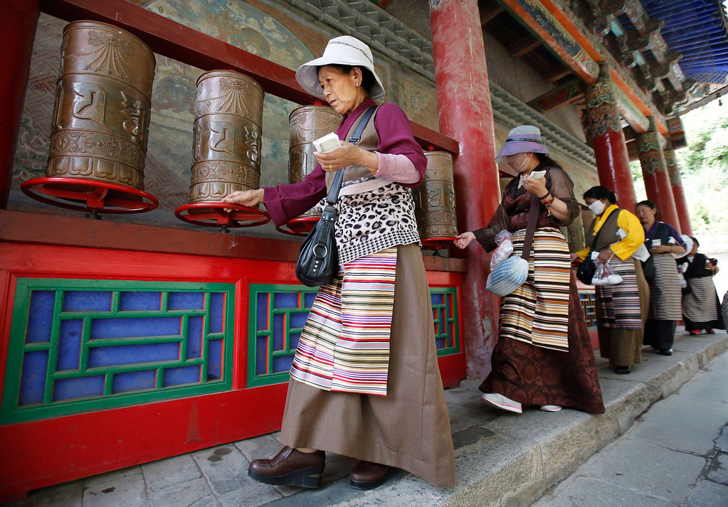 . Tibetan women spin prayer wheels at Kumbum monastery, where Dalai Lama used to live, on the outskirts of Xining, Qinghai province, July 6, 2013. The streets of Chabcha county in western Qinghai province were quiet on Saturday as Tibetan monks marked the Dalai Lama\'s birthday in their homes, wary that any public celebration could endanger a tentative softening by Chinese authorities. REUTERS/Kim Kyung-Hoon