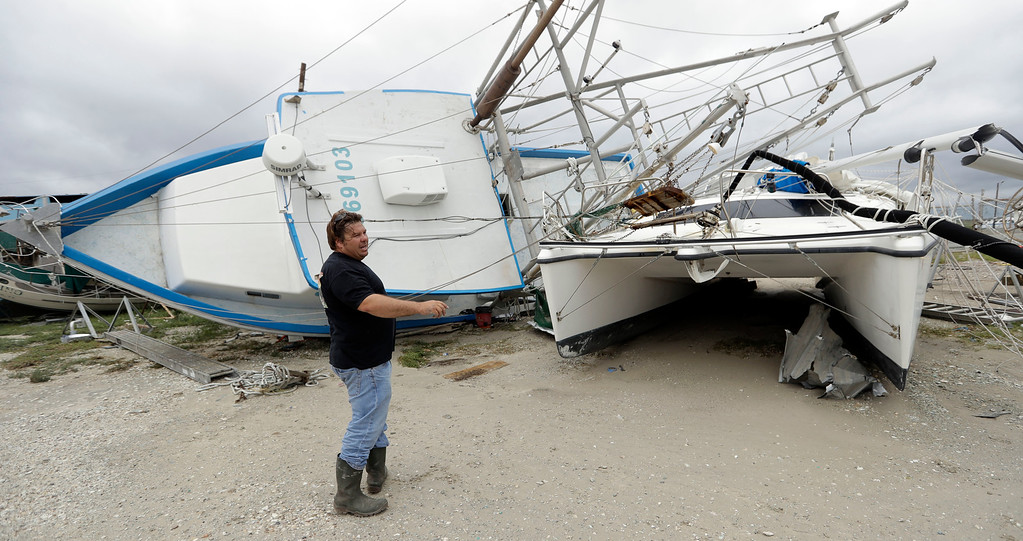 """. Lee Morris checks on his shrimp boat \""""Bad Idea\"""", left, that was damaged in the wake of Hurricane Harvey, Sunday, Aug. 27, 2017, in Rockport, Texas. (AP Photo/Eric Gay)"""