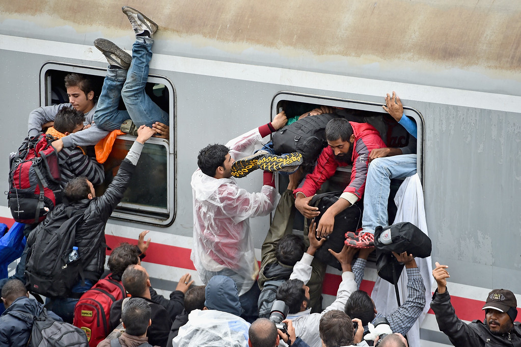 . Migrants desperately try and board a train heading for Zagreb from Tovarnik station on September 20, 2015 in Tovarnik,Croatia. Croatia continues to send buses and trains north to its border with Hungary, as officials have estimated the around 20,000 migrants have entered since Wednesday.  (Photo by Jeff J Mitchell/Getty Images)
