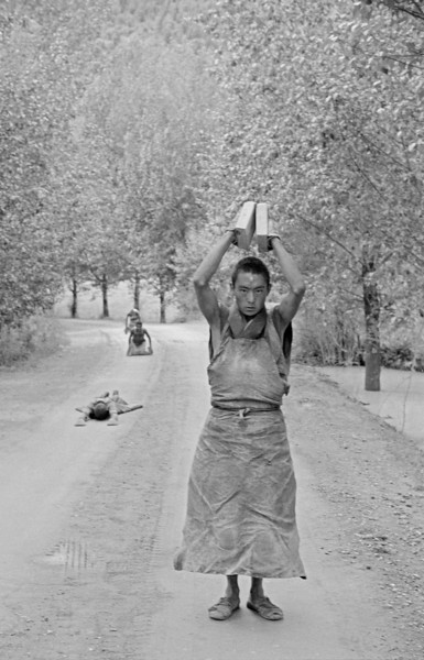 Covering several miles a day, monk pilgrims from Kham prostrate the full length of their bodies along ancient pilgrim routes. Over a thousand miles remain before they will reach their destination, Lhasa.  Kham, Tibet 1991.