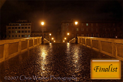 About.Com:Photography  Finalist Image by Chris Washer for Weekly Assignment 16 - Night  This image makes excellent use of leading lines to draw the viewer into the image. The simple composition helps to add to the leading lines effect as well. The texture of the walkway and the light reflecting on the walkway help to add interest to the image.  January 3, 2008