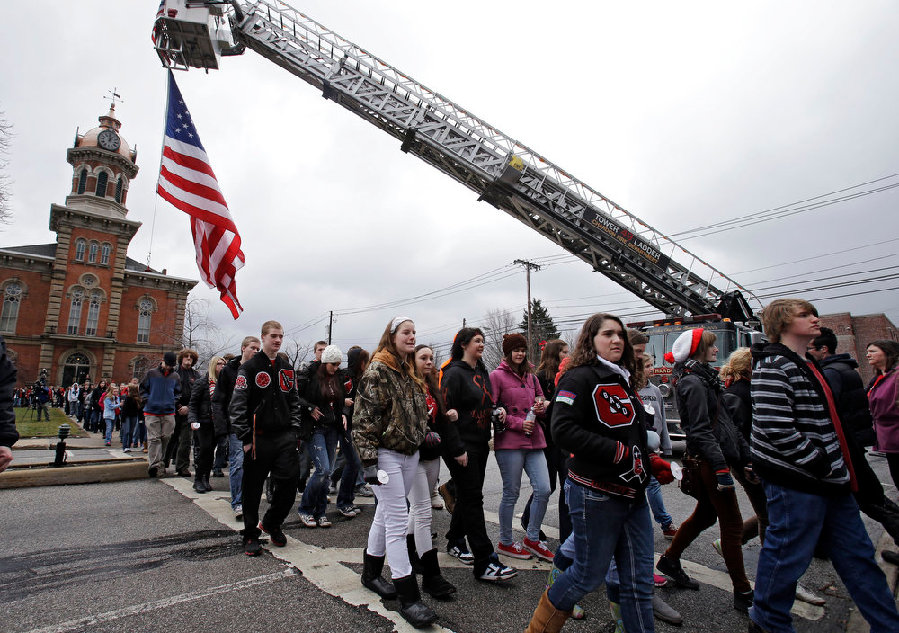. Chardon High School students walk under a large American flag on the town square in Chardon, Ohio Wednesday, Feb. 27, 2013 during a memorial march for 3 students killed in a shooting at the school last year. Students walked from the school to the town square for a memorial commemoration. The march ended at the courthouse where 18-year-old shooter T.J. Lane pleaded guilty to all charges in February. (AP Photo/Mark Duncan)