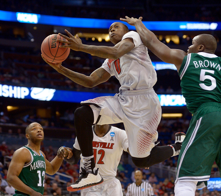 . Louisville guard Terry Rozier (0) drives for the basket as Manhattan forward Rhamel Brown (5) defends during the first half in a second-round game in the NCAA college basketball tournament Thursday, March 20, 2014, in Orlando, Fla. (AP Photo/Phelan M. Ebenhack)