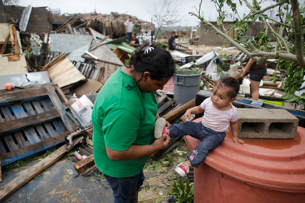 . Maria Ramirez, left, puts the shoes on her one-year-old niece Maritza next to the remains of their home that was destroyed by Hurricane Odile in Los Cabos, Mexico,  Monday, Sept. 15, 2014. (AP Photo/Victor R. Caivano)
