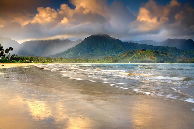 The mist and cloud set the mood on this memorable morning.  Clear skies would have been nice to walk under, but the mood would have been gone and the light would have been harsh.  Hanalei Bay is a 3-mile long perfect crescent of sand surrounded by the world's rainiest mountains. Over 500 inches of rain drench nearby Mt. Waialeale every year and about 100 inches fall on this beach. Despite all that rain, days are mostly clear so it still took me several return trips to this beach in order to be here at the right time.  Up to seven waterfalls are often seen in the mountains after a good rain shower.   The atmosphere created some nice  warm filtered light, which turned the sand into gold for a few seconds in between waves.