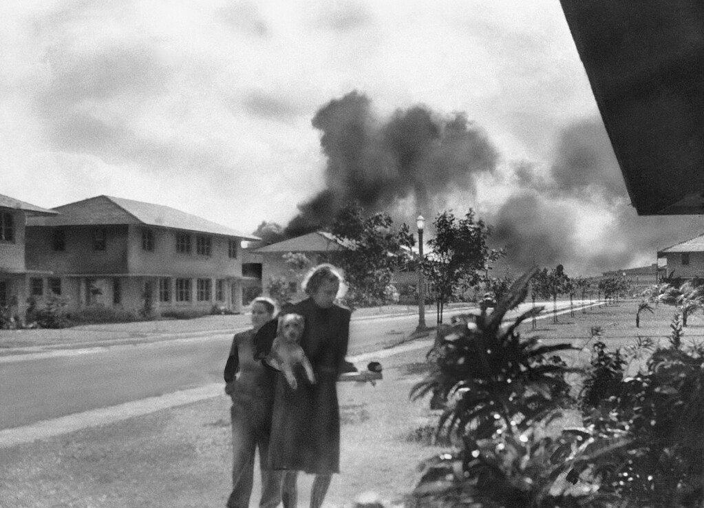 ". An unidentified officers\' wife, investigating explosion and seeing smoke pall in distance at 8:15 am Dec. 7, 1941, heard neighbor Mary Naiden, then an army hostess, exclaim �There are red circles on those planes overhead. They are Japanese!""  A boy and a woman carrying a dog flee toward quarters.  (AP Photo/Mary Naiden)"