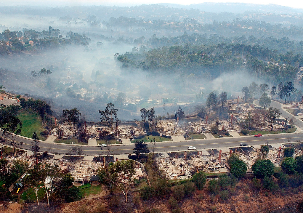 . Smoke rises from burned home in the the Scripps Ranch neighborhood of San Diego  Oct. 27, 2003. When the western edge of the fast-moving Cedar Fire entered San Diego on Oct. 26, it destroyed more than 300 homes in the  bedroom community of 30,000 people.  (AP Photo/Denis Poroy)