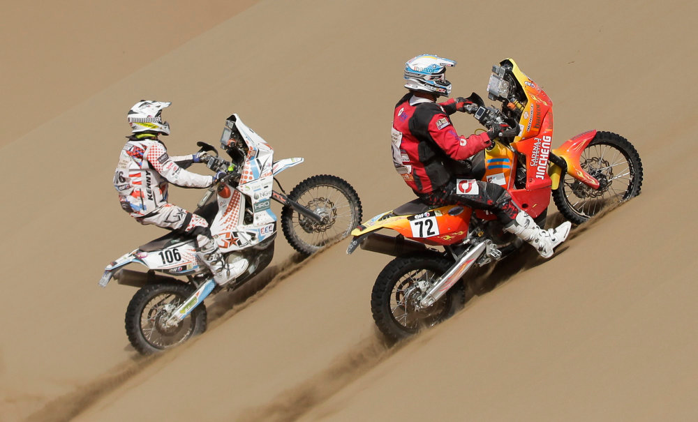 Description of . In this Jan. 10, 2013 photo, KTM rider Thomas Bourgin of France, left, and Jincheng rider Pablo Pascual of Argentina compete in the 6th stage of the 2013 Dakar Rally from Arica to Calama, Chile. Bourgine died on Jan. 11, 2013 in an accident during the 7th stage of the Dakar Rally between Calama, Chile, and Salta, Argentina. (AP Photo/Victor R. Caivano)