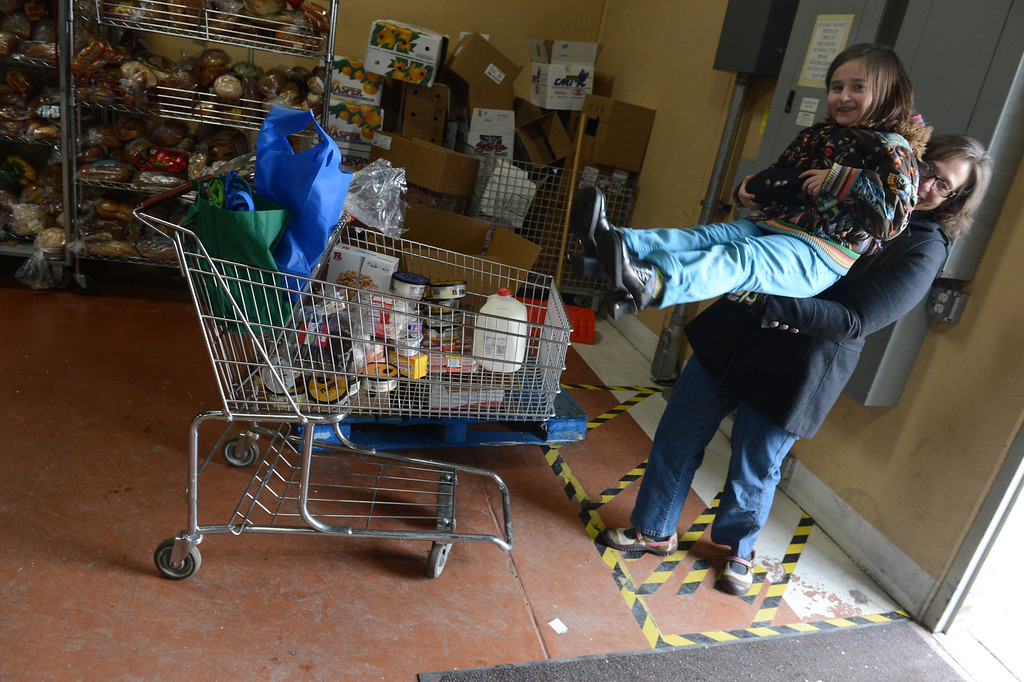 . Robyn Van Matre lifts her daughter, Hope,, from a shopping cart after visiting the Community Food Share in Longmont, CO, Thursday December 27, 2012. Craig F. Walker, The Denver Post