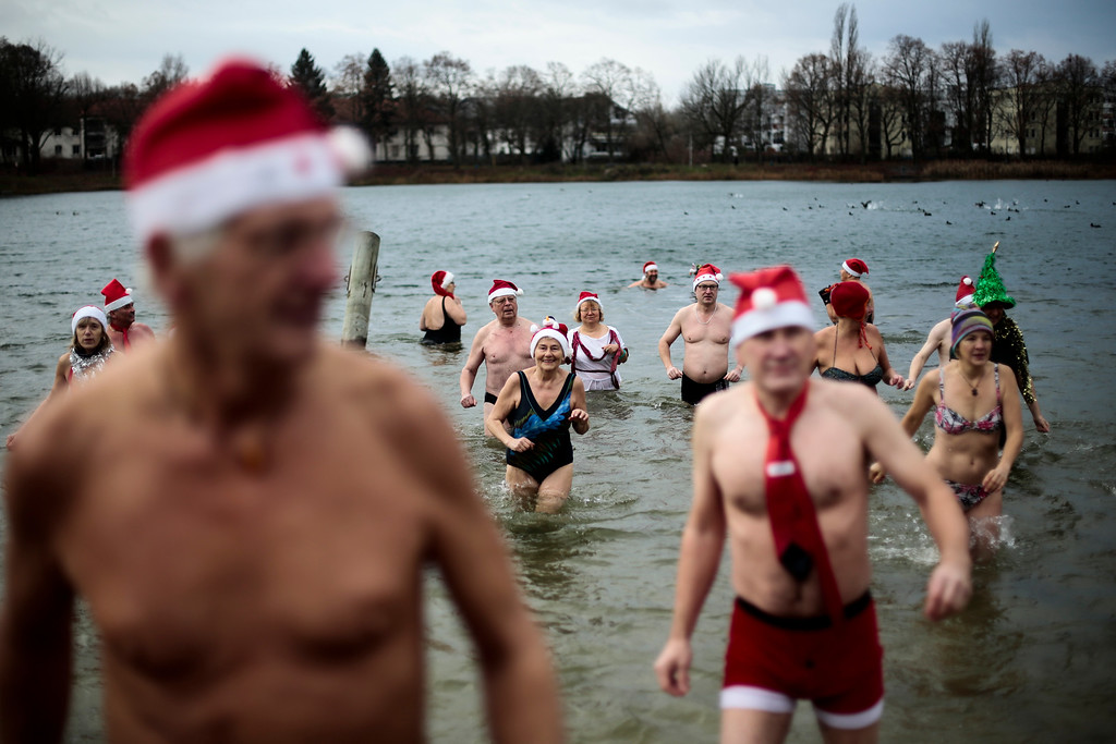 . Members of the winter and ice swimming club \'Seehunde Berlin\' (Berlin Seals), wearing Christmas themed hats, attend the annual Christmas swim at the chilly Oranke Lake in Berlin, Thursday, Dec. 25, 2014. Every Christmas the club arrange a swim at the lake. (AP Photo/Markus Schreiber)