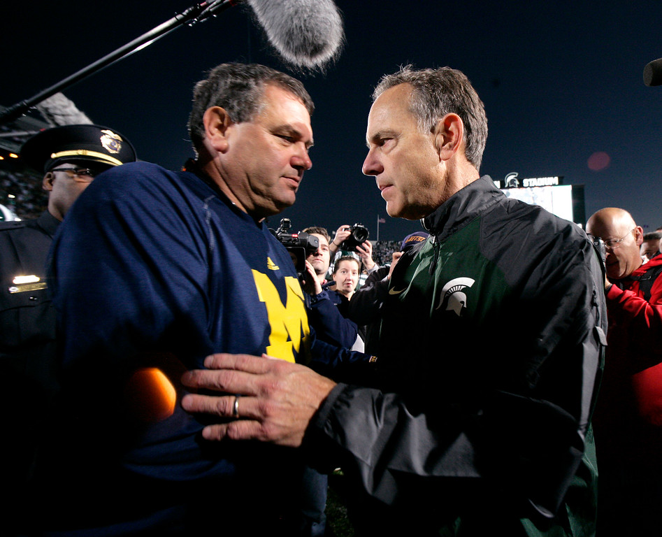 . Michigan coach Brady Hoke, left, and Michigan State coach Mark Dantonio shake hands following an NCAA college football game, Saturday, Oct. 25, 2014, in East Lansing, Mich. Michigan State won 35-11. (AP Photo/Al Goldis)