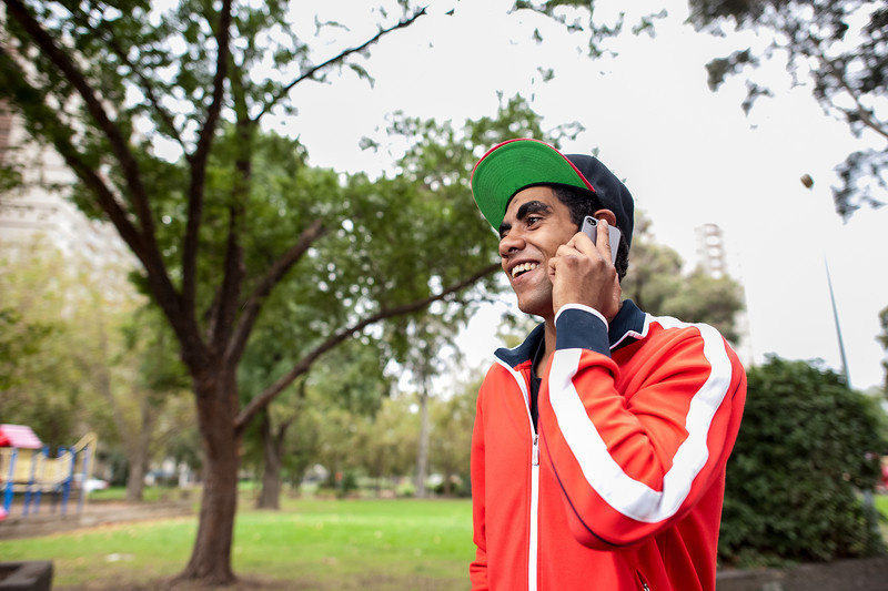 Aboriginal man in a red top on the phone