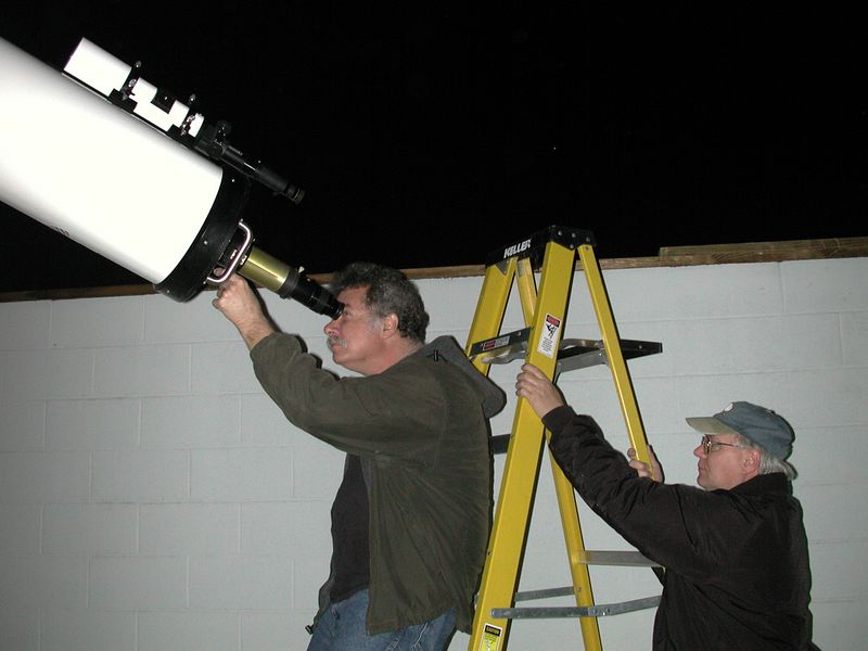 Al Paslow, me observing with the 10 inch f-12 Refracting telescope at Mingo Observatory, in Washington County Pennsylvania in October 2004. Eugene Kulakowski, of Cannonsburg, PA helps steady the ladder.