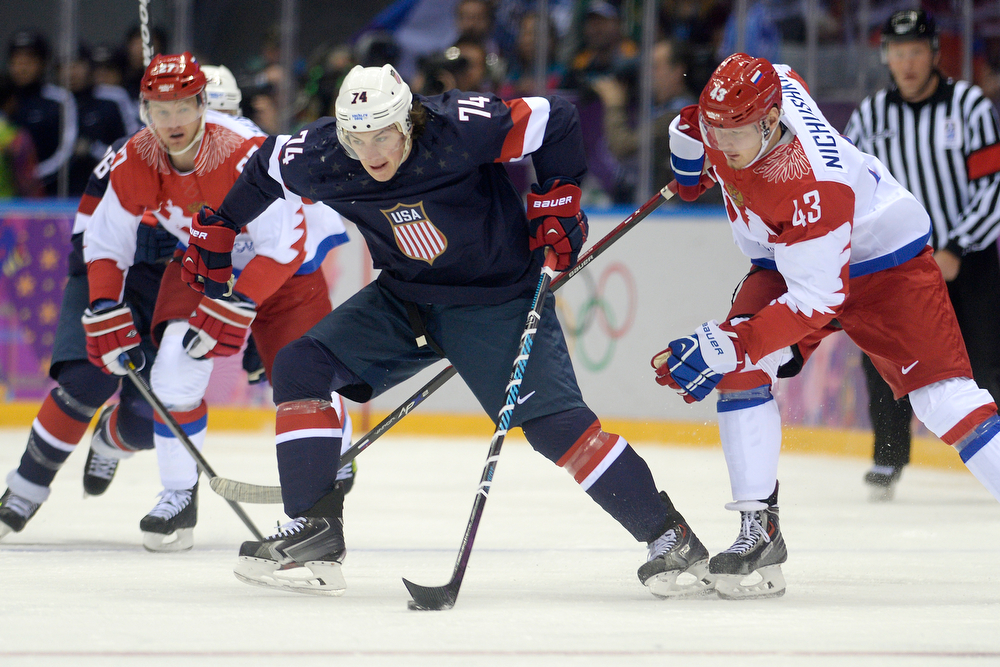 . T.J. Oshiet (74) of the U.S.A. controls the puck as Valeri Nichushkin (43) of the Russia defends during the first period of men\'s hockey action at Bolshoy arena. Sochi 2014 Winter Olympics on Saturday, February 15, 2014. (Photo by AAron Ontiveroz/The Denver Post)