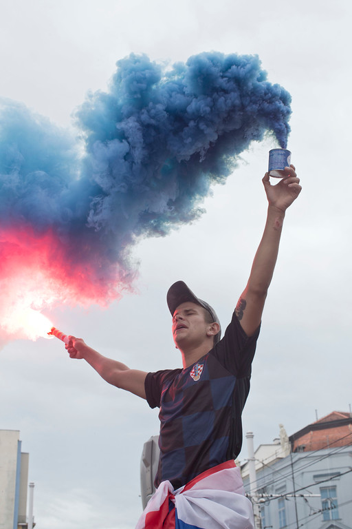 . A Croatian soccer fan holds a flare and a smoke bomb before the start of the World Cup final in central Zagreb, Croatia, Sunday, July 15, 2018. Croatia\'s national soccer team faces France in the World Cup final in Russia. (AP Photo/Marko Drobnjakovic)