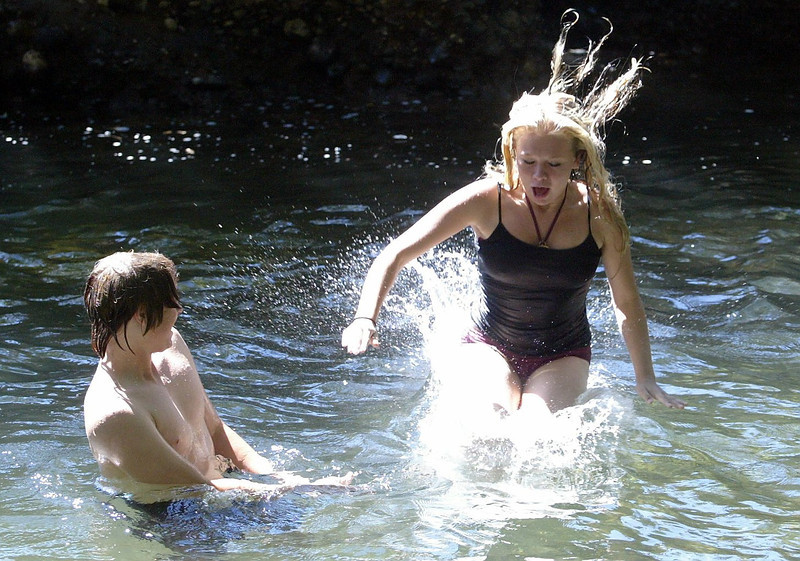 "Adam Silkwood, 16, watches Cheri Clark, 13, swing off a rope swing into a well-known swimming hole known as ""The Bank"" located along Vallombrosa Ave. near Manzanita Ave. on Chico Creek Thursday - halley photo 7/6/06"