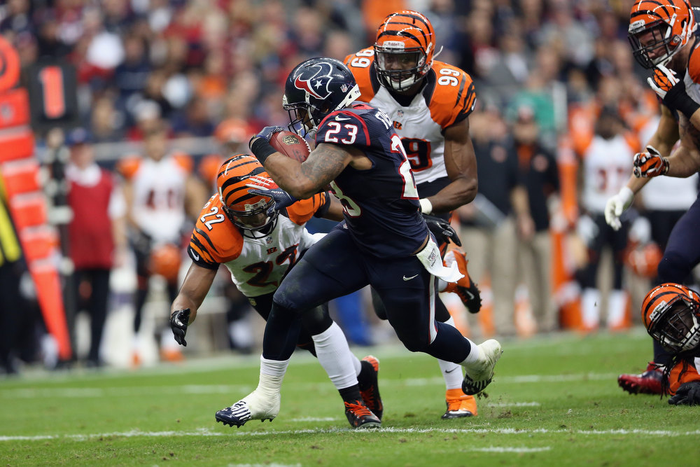 . Arian Foster #23 of the Houston Texans runs the ball against Nate Clements #22 of the Cincinnati Bengals during the AFC Wild Card Playoff Game at Reliant Stadium on January 5, 2013 in Houston, Texas.  (Photo by Ronald Martinez/Getty Images)