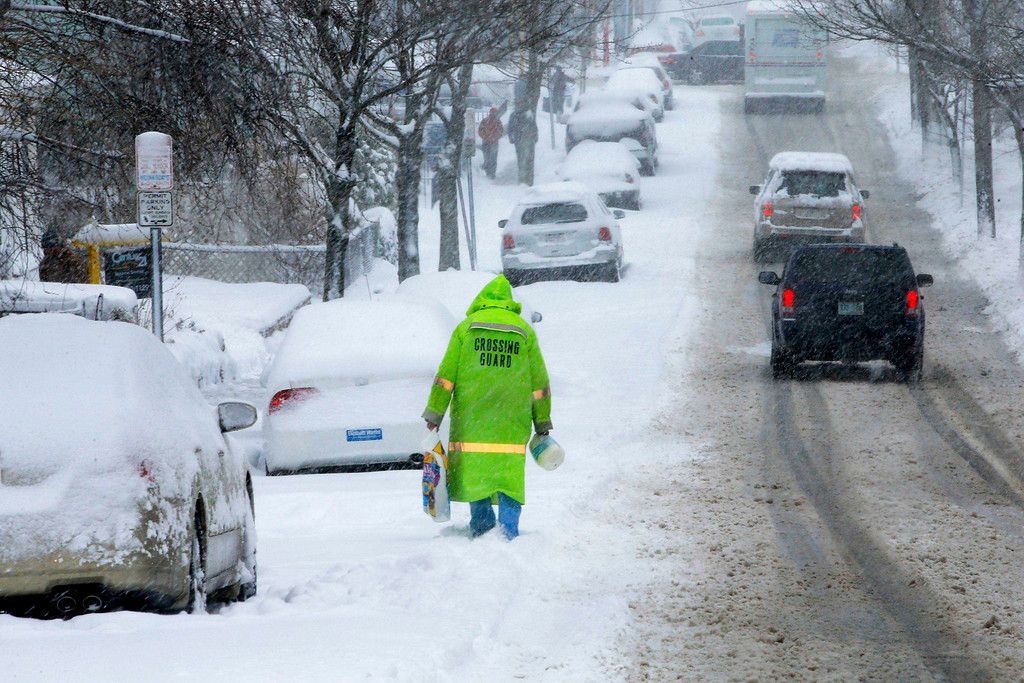 . A crossing guard walks down a snow-covered street in Somerville, Massachusetts March 8, 2013.     REUTERS/Brian Snyder