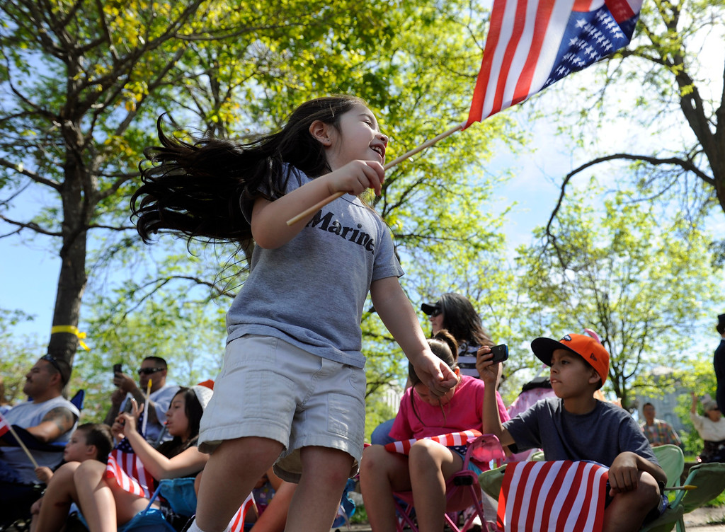 . Alena Martinez, 2, joins her family (including her mother in the background who served in the Marines) on Broadway, waving flags and taking photos. (Photo By Kathryn Scott Osler/The Denver Post)