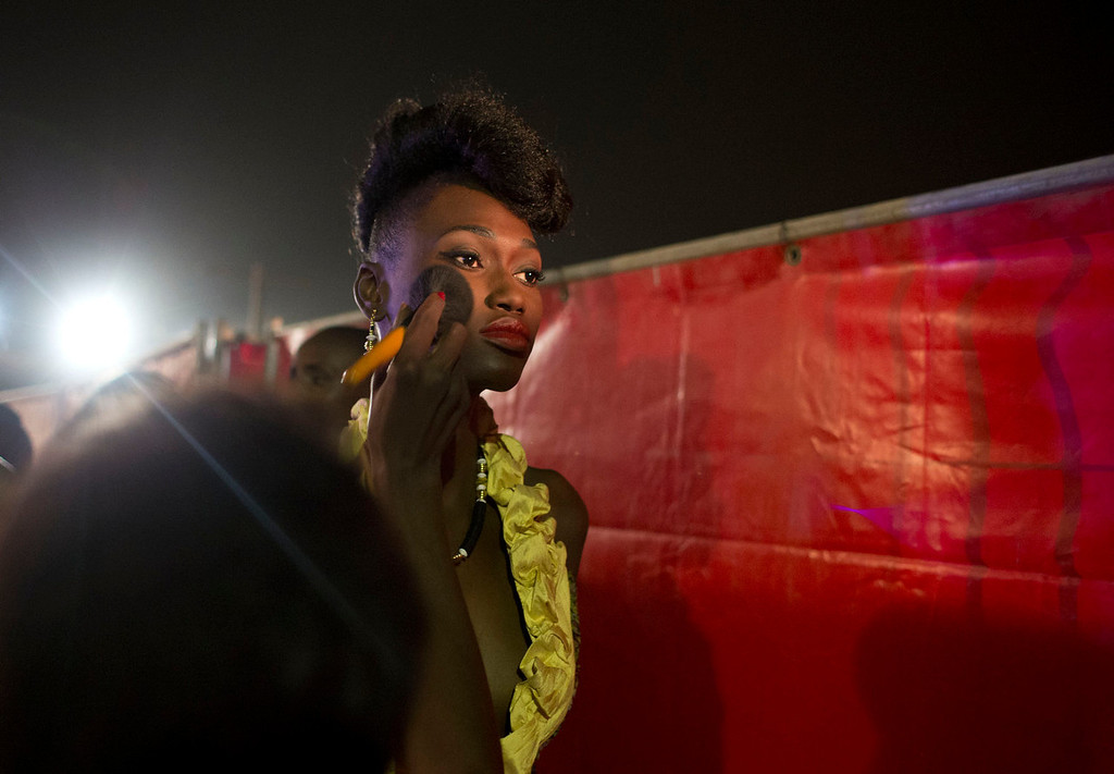 . A model gets a last minute makeup touch up as she prepares to walk the runway in a design by designer Weni of Benin, at Hotel des Almadies, in Dakar, Senegal, in the early morning hours of Sunday, June 23, 2013. After a Friday show held in a dusty marketplace in the working class suburb of Guediawaye, the runway finale of Dakar Fashion Week was held at a luxury hotel and showcased the work of 14 designers from West Africa, Europe, South America, and the Caribbean. (AP Photo/Rebecca Blackwell)