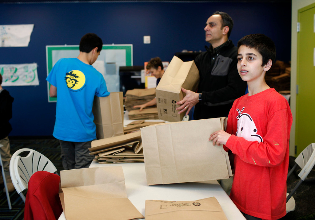 . Shaan Singh, 13, right, doubles up brown bags for Sunnyvale Community Services during the sixth annual Mitzvah Day for the Martin Luther King Jr. Day of Service at the Palo Alto Jewish Community Center in Palo Alto, Calif., on Monday, Jan. 21, 2013. Volunteers worked on 27 community projects on and off campus on Monday. The bags will be later used by the Sunnyvale group to distribute food for families. (Kirstina Sangsahachart/Staff)