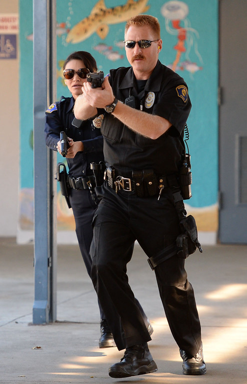 . The Hermosa Beach and Manhattan Beach Police Depts. conducted an active shooter drill on the campus of Hermosa Valley School Monday, November 25, 2013, Hermosa Beach, CA.   Officers responded to staged calls of a gun man on the campus, had to find and neutralize the suspect. Students also participated in the drill to give it more realism.  Officers run onto campus into the direction of the shooting. Photo by Steve McCrank/DailyBreeze